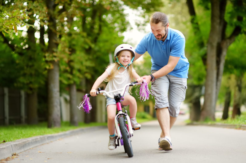 father teaches daughter ride cycle